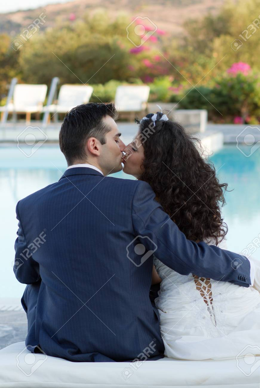 Happy new family sitting at the pool kissing Stock Photo - 15980705