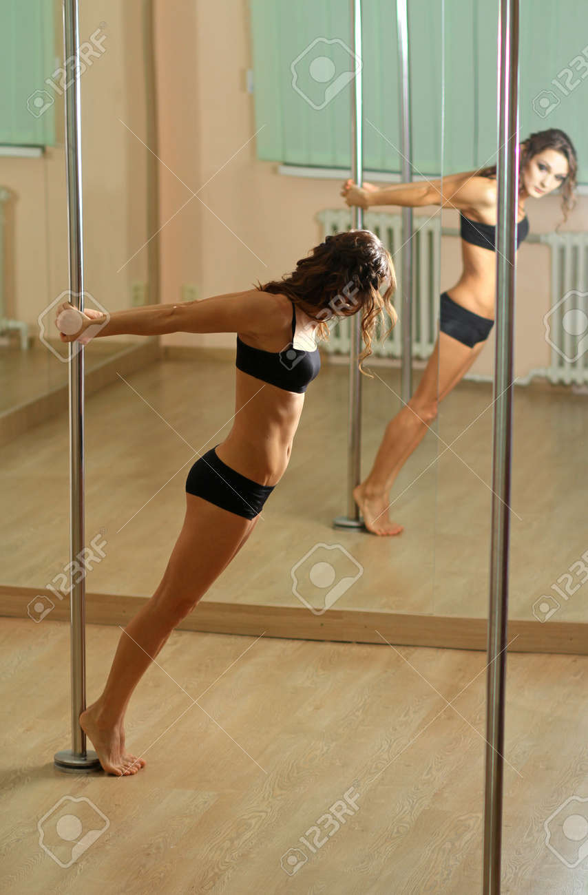 Stock Photo - Young professional pole dancer exercising in the studio in  strip plastic dance