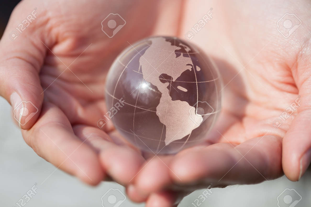 Model holding a glass globe in hands  Good concept for care,
