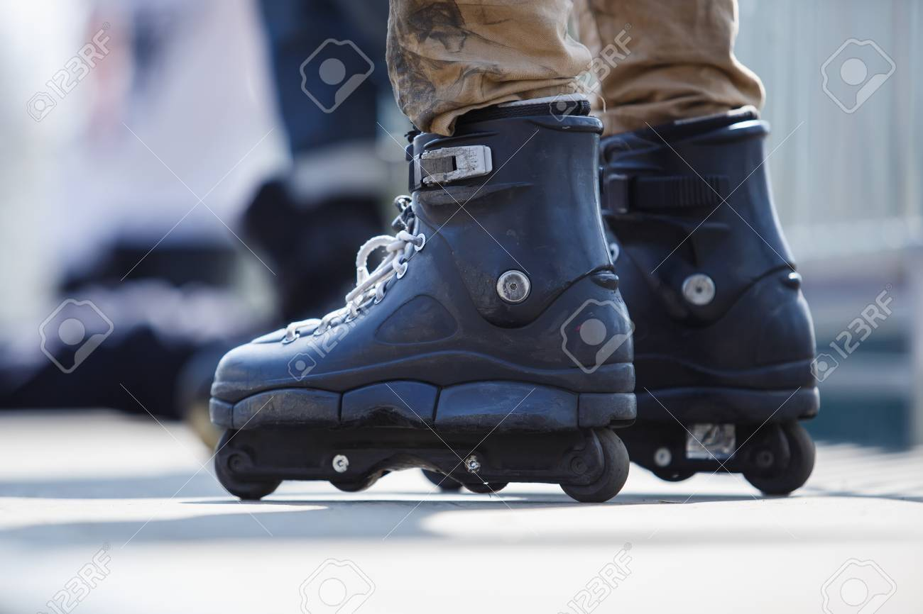 Aggressive inline roller blader wearing big black skates for extreme skating.Feet of young athlete in in-line blades exercising in skatepark outdoor in summer - 106085809