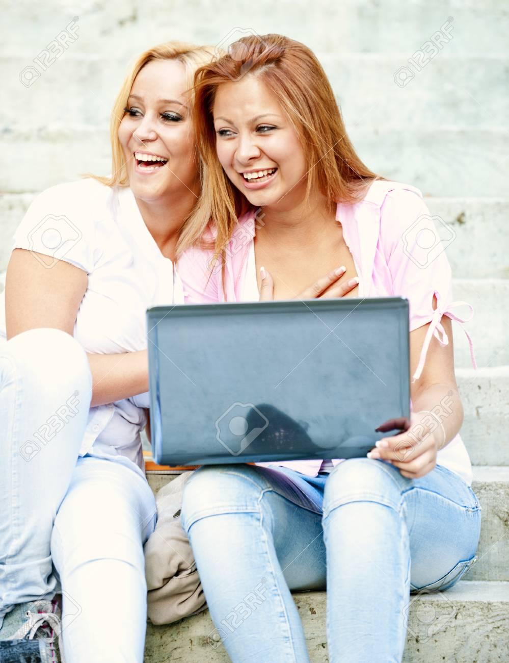 84070c541 Felices jóvenes estudiantes de secundaria o universitarias sentados en los  pasos fuera de la escuela carcajadas y un descanso de la escuela con una ...