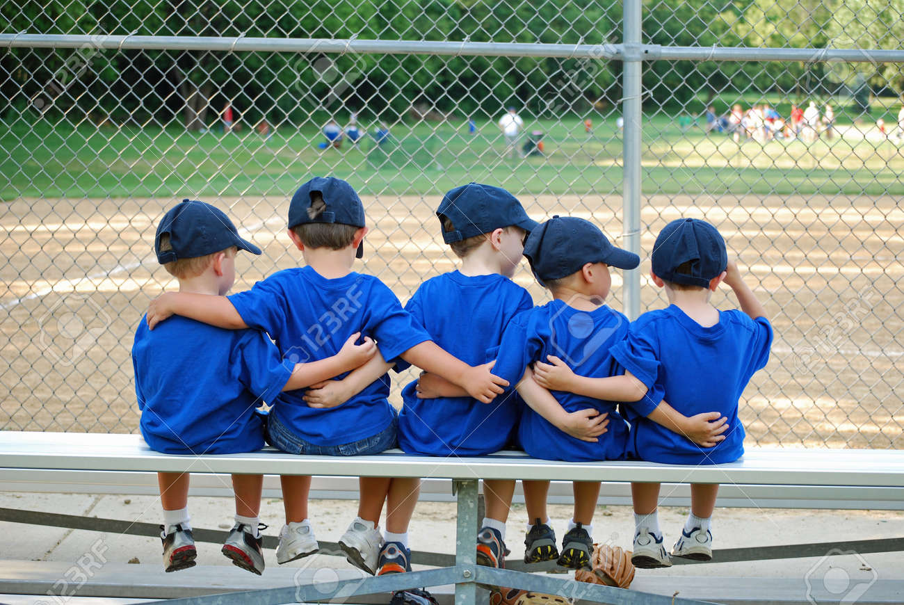 five little boys put their arms around each other while waiting