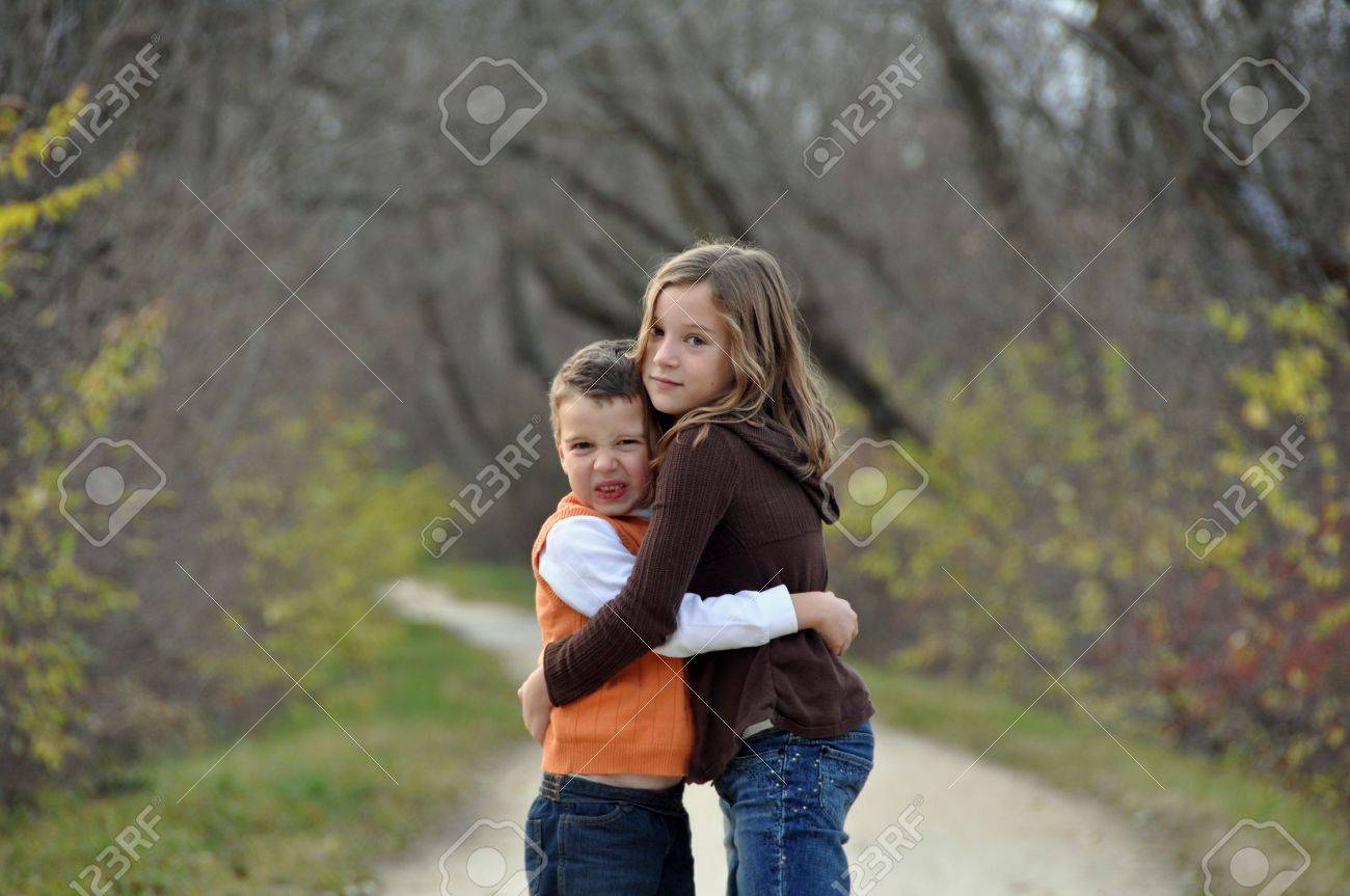 a crabby boy and his sister hug on an autumn day Stock Photo - 6353041
