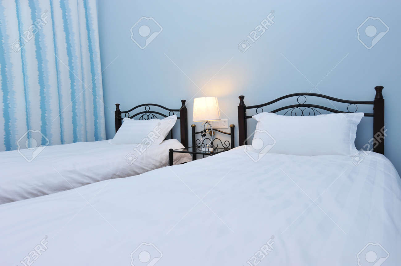 Two beds bedroom with bedside table and lamp Stock Photo - 13253140