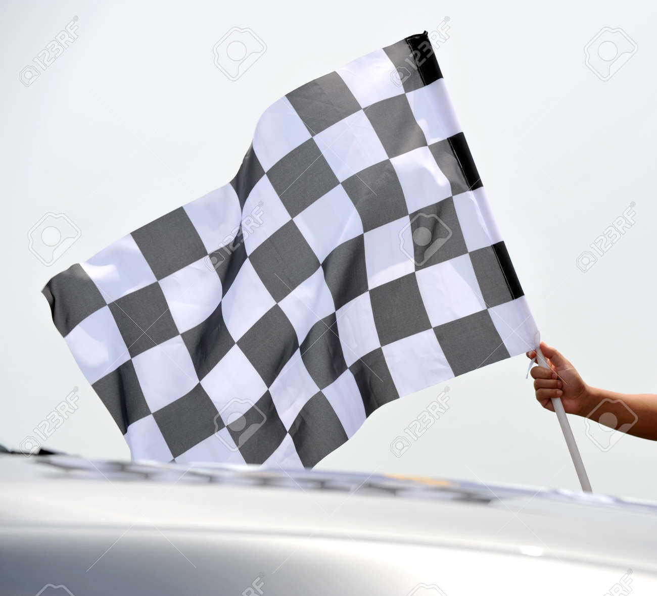 checkered race flag in hand. Stock Photo - 13344623