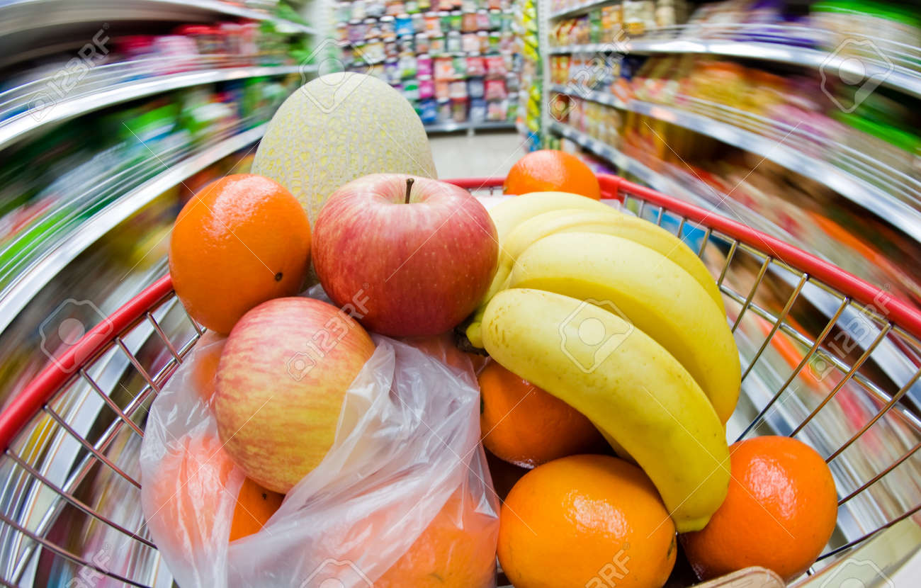 Moving shopping cart, and shot with a slow shutter from the shopper's point of view. The fruits in the shopping cart is in focus, and the supermarket is motion-blurred. Stock Photo - 13694699