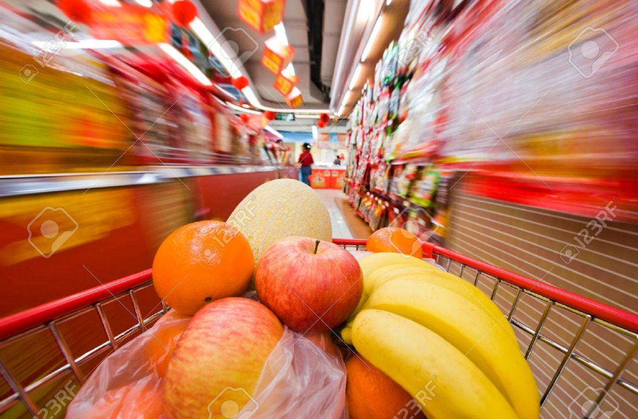 Moving shopping cart, and shot with a slow shutter from the shopper's point of view. The fruits in the shopping cart is in focus, and the supermarket is motion-blurred. Stock Photo - 13695300