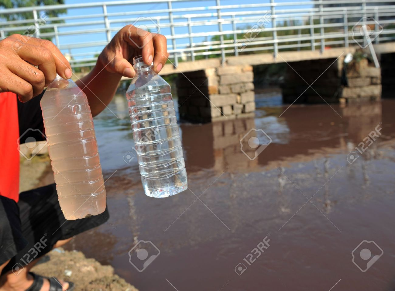 two bottles in people hands with clean and dirty water. Stock Photo - 13829692