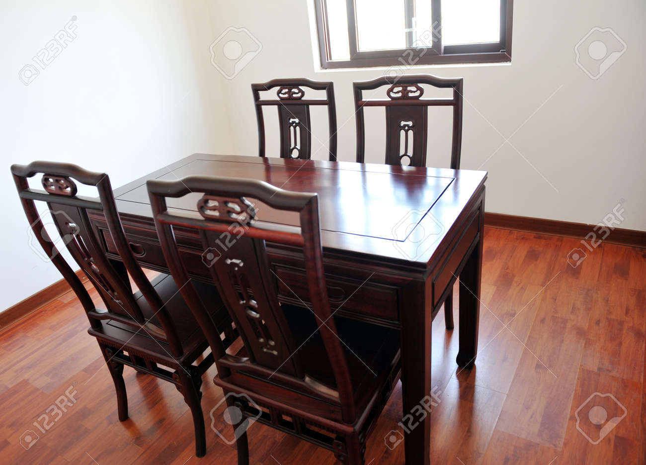 123RF.com & Chinese dining room with dark wood table four chairs and window..