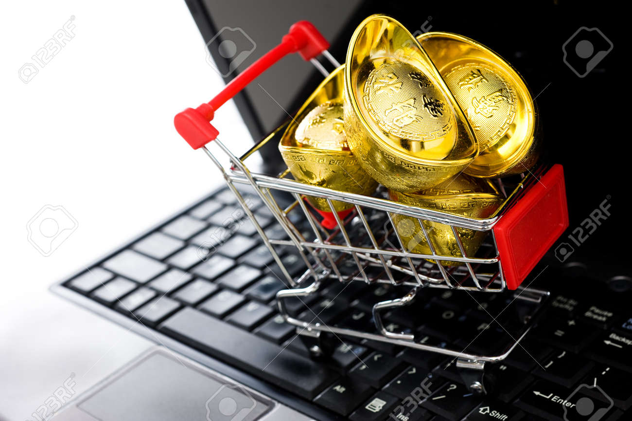 shopping cart full of Chinese gold ingot ornaments on the laptop, on-line shopping concept. Stock Photo - 13863737