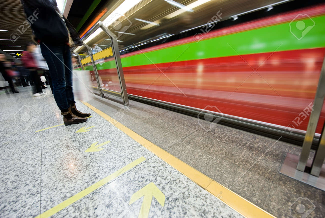People waiting in subway station with motion blurred train beside. Stock Photo - 13955116