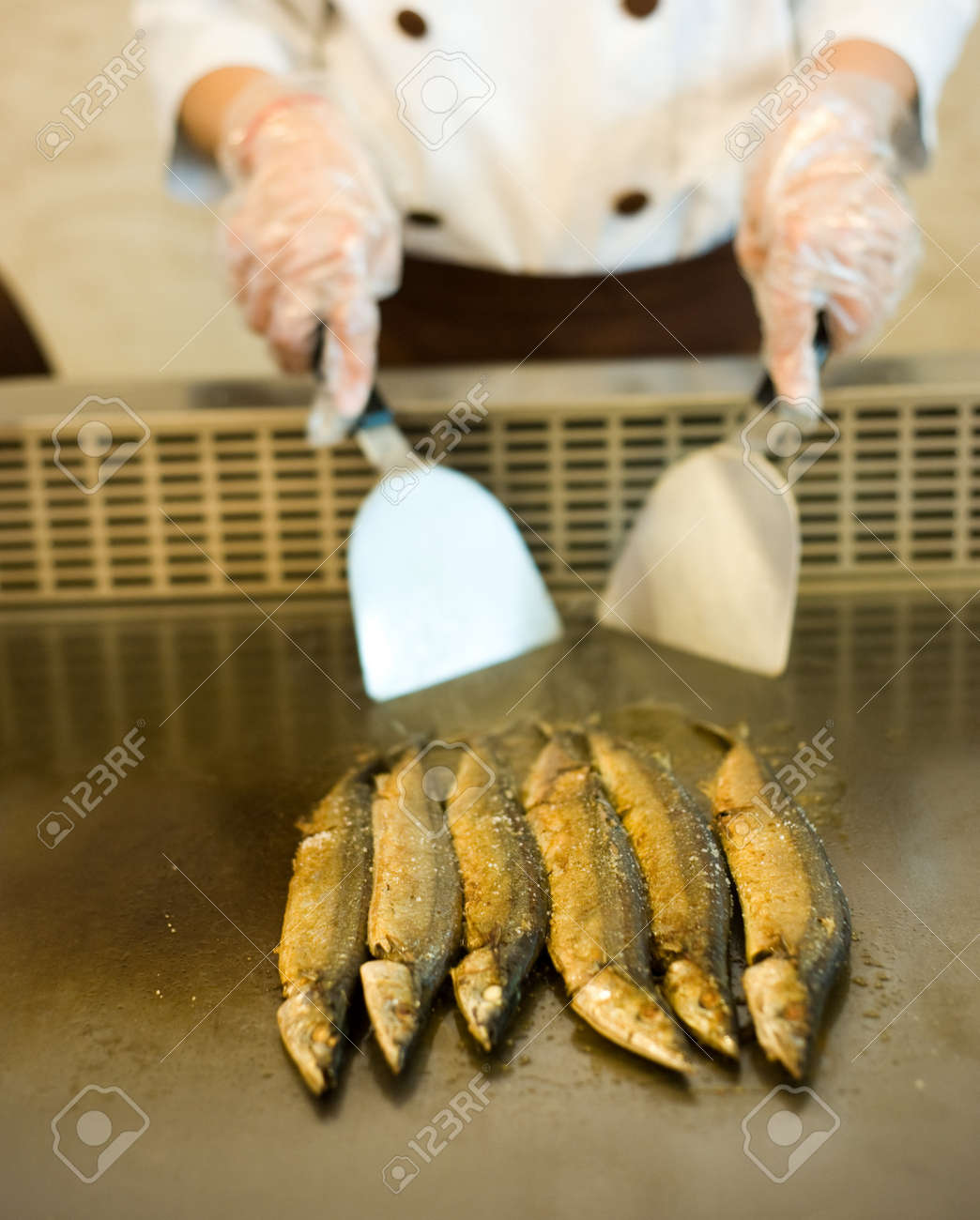 Japanese chef cooking traditional saury teppanyaki on a hot plate. Stock Photo - 14053233