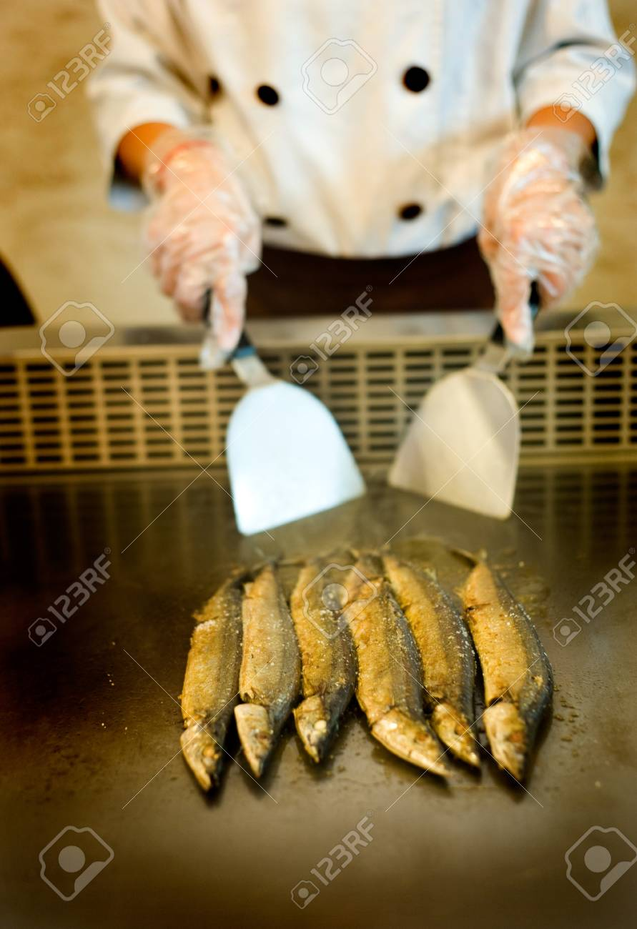 Japanese chef cooking traditional saury teppanyaki on a hot plate. Stock Photo - 14053257