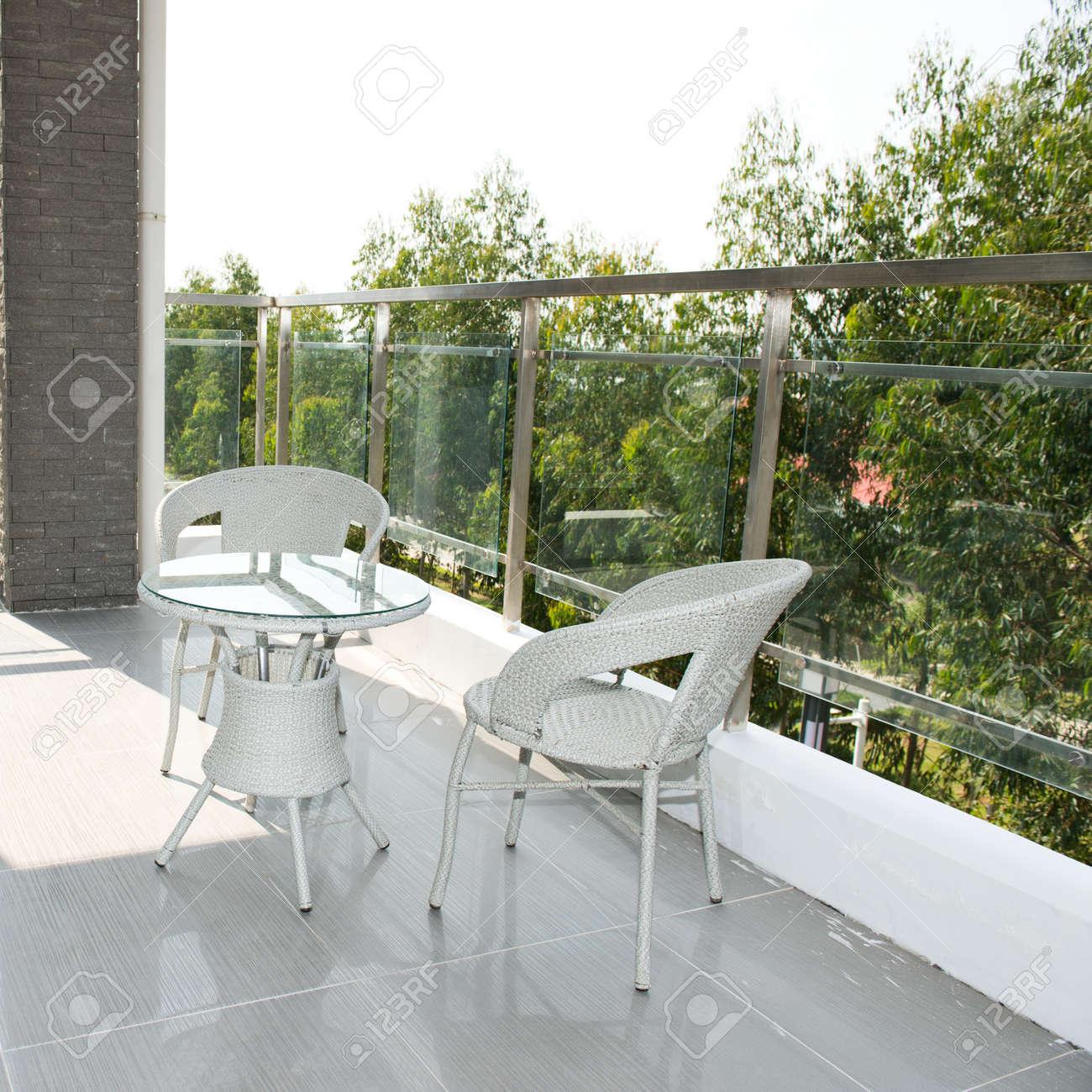 balcn con mesa y sillas blancas en una casa grande foto de archivo