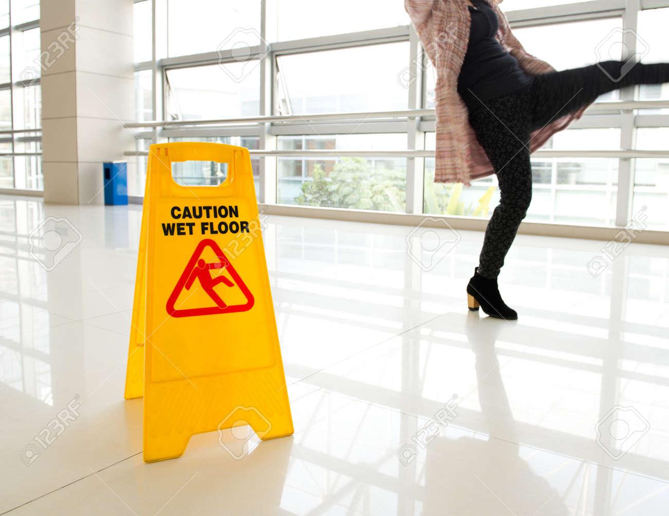 Woman slips next to wet floor sign - 20227163