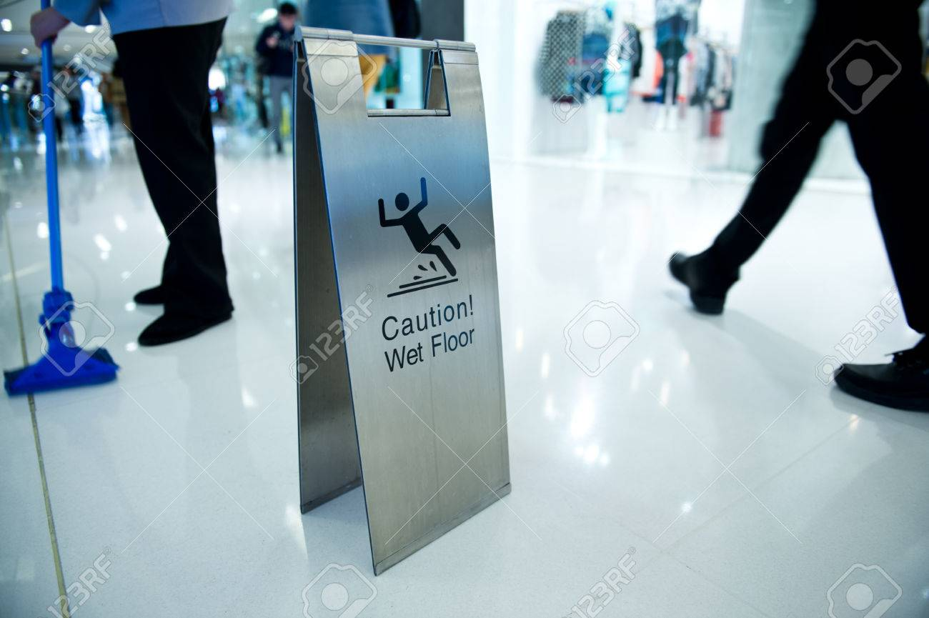 cleaning in progress, and wet floor caution sign besides. - 22994134