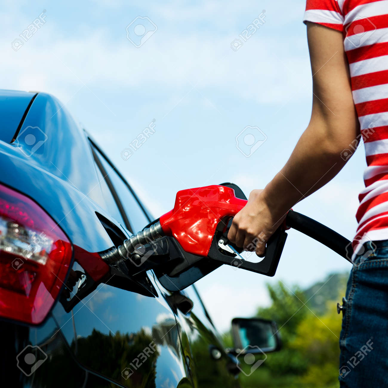Hand refilling the car with fuel. Stock Photo - 33756945