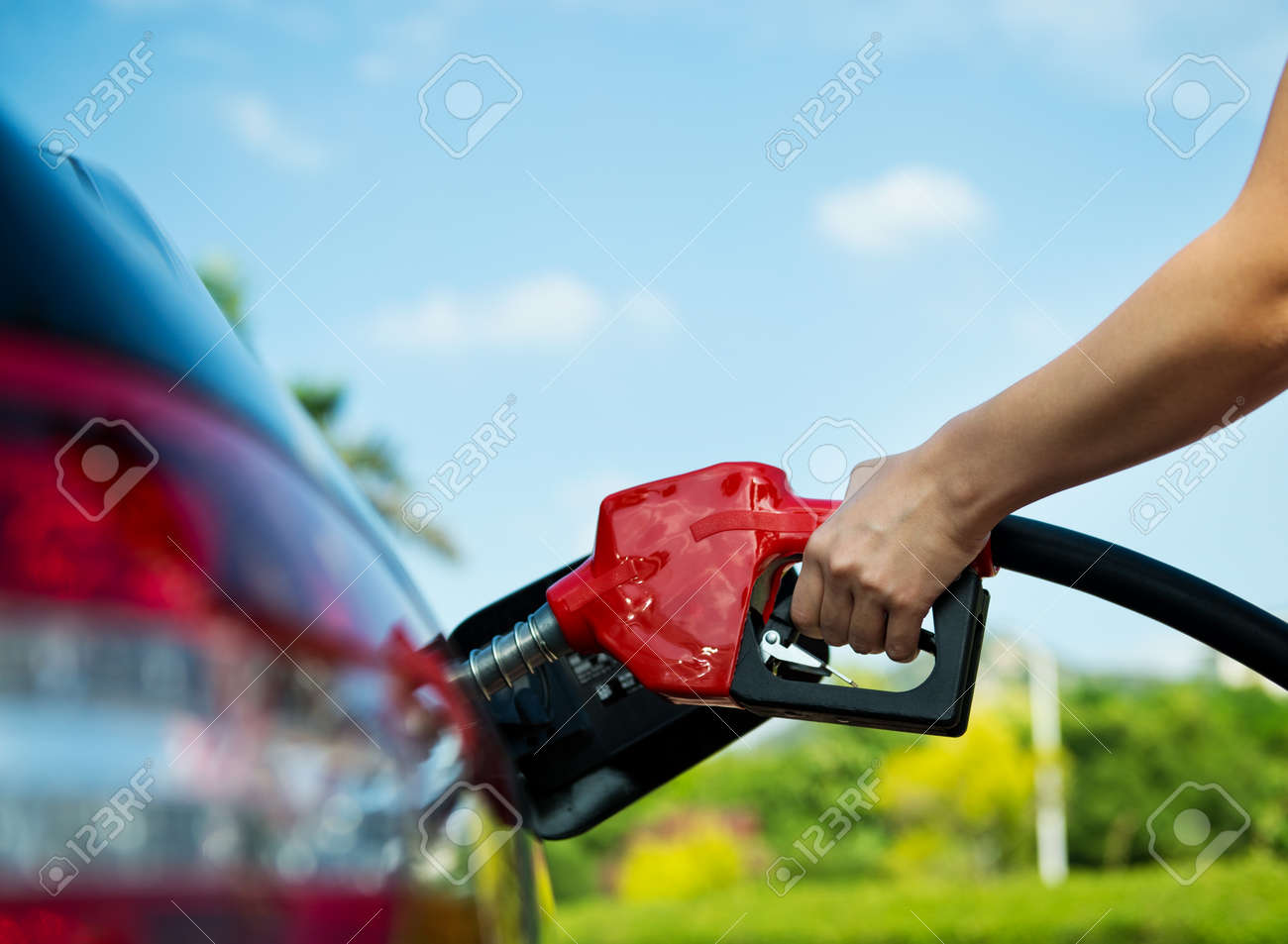 Hand refilling the car with fuel. - 33782476