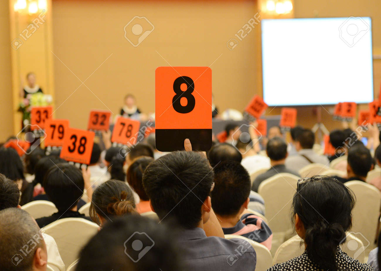 People holding auction paddle to buy from auction. Stock Photo - 33783596