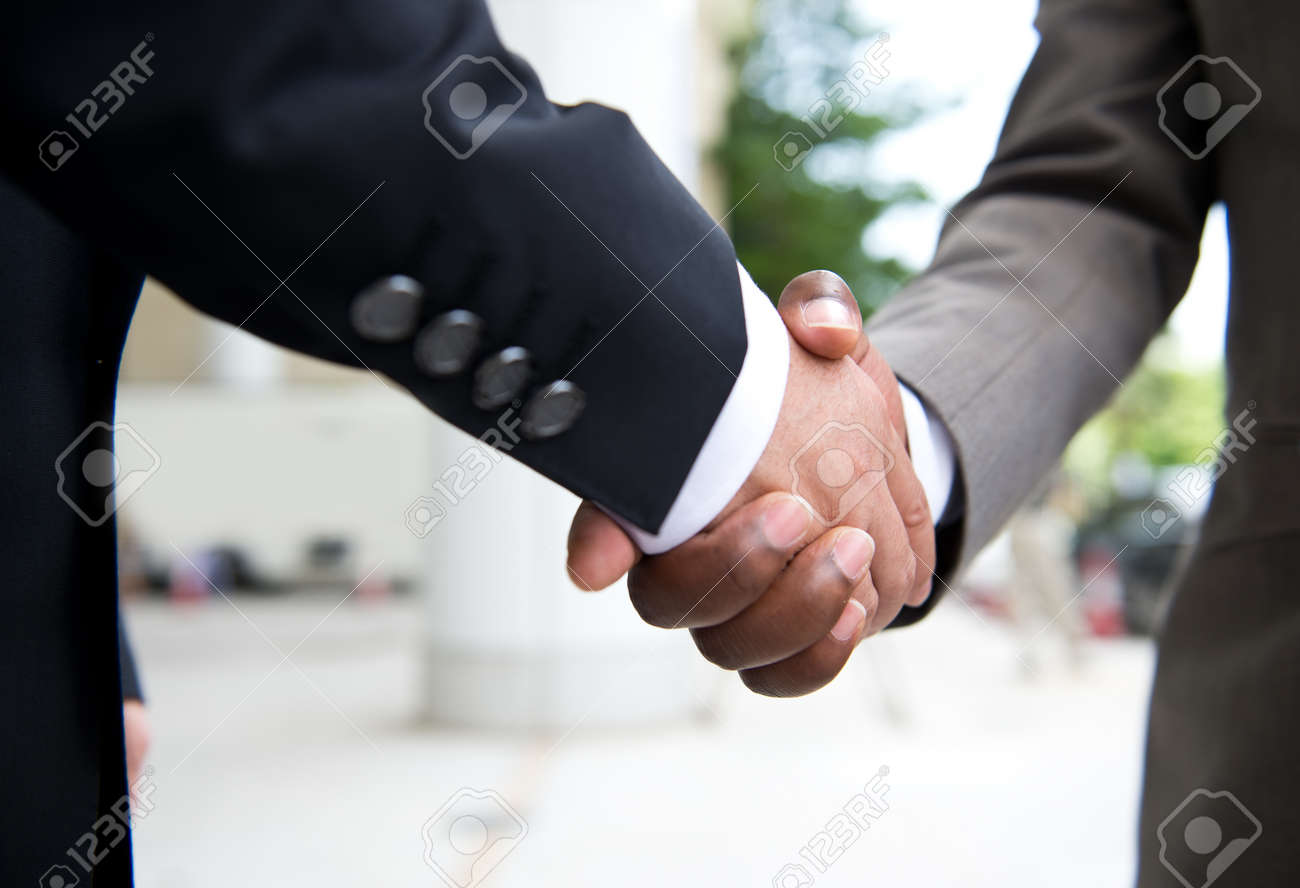 African businessman's hand shaking white businessman's hand  making a business deal. Stock Photo - 33791024
