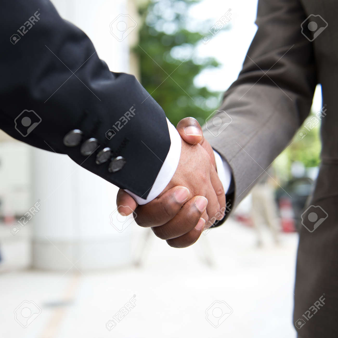 African businessman's hand shaking white businessman's hand  making a business deal. Stock Photo - 33791032
