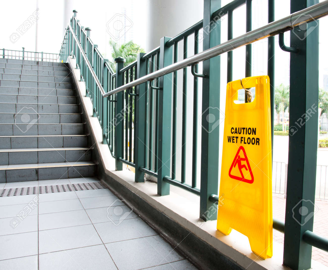 Wet floor caution sign near the stairs. - 35184492