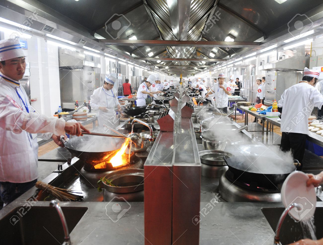Fujian-April 14, 2010.  Group of chefs working together in a Chinese restaurant kitchen, Fujian province, China. Stock Photo - 37181499