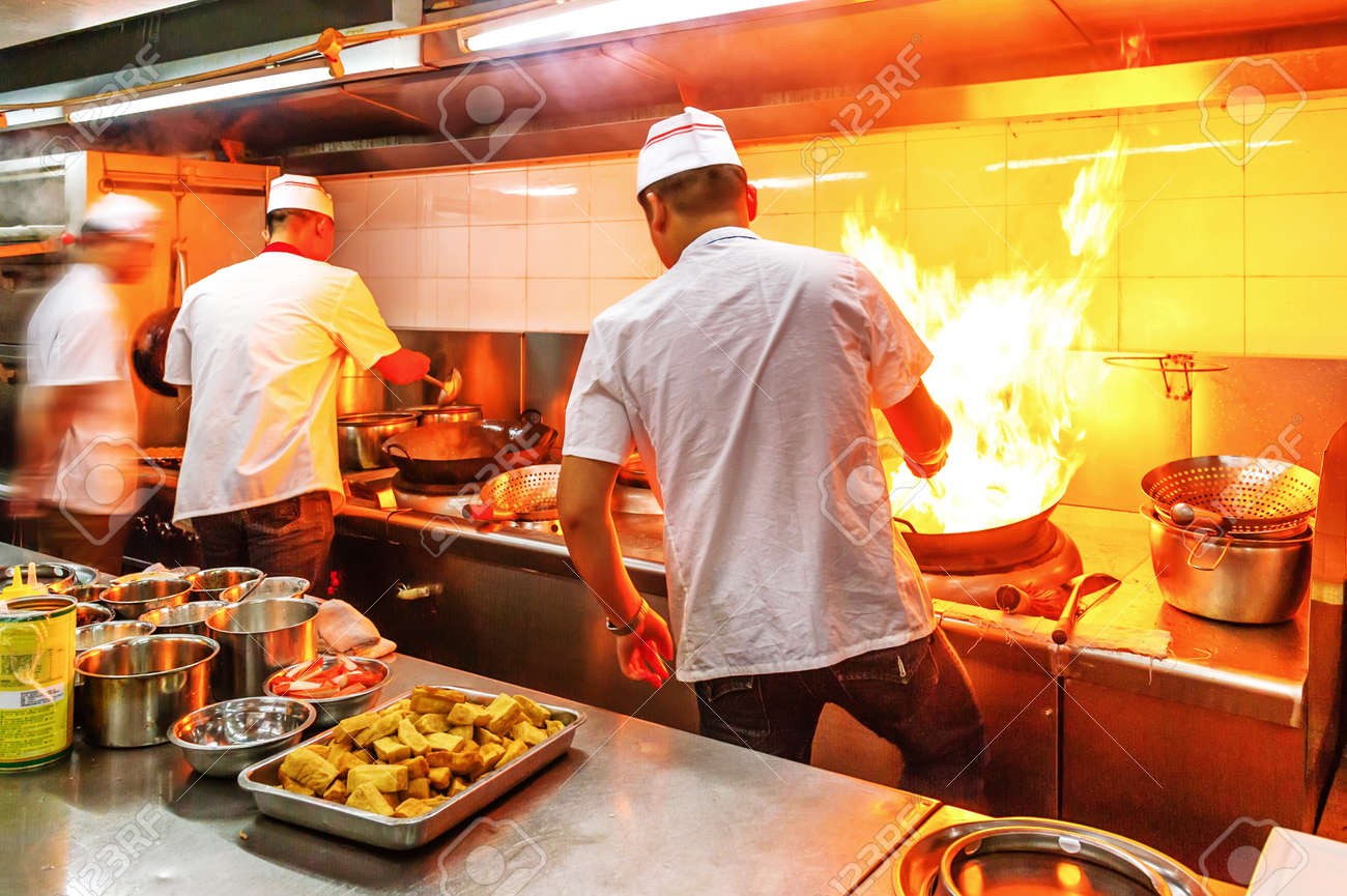 Chef in restaurant kitchen at stove with pan, doing flambe on food - 35773854