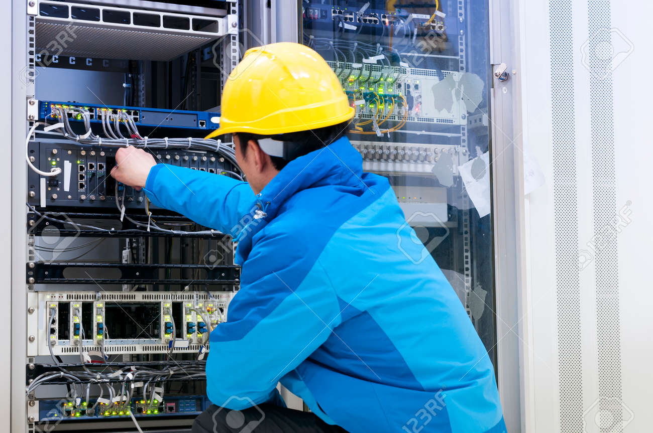 Man connecting network cables to switches - 35775702