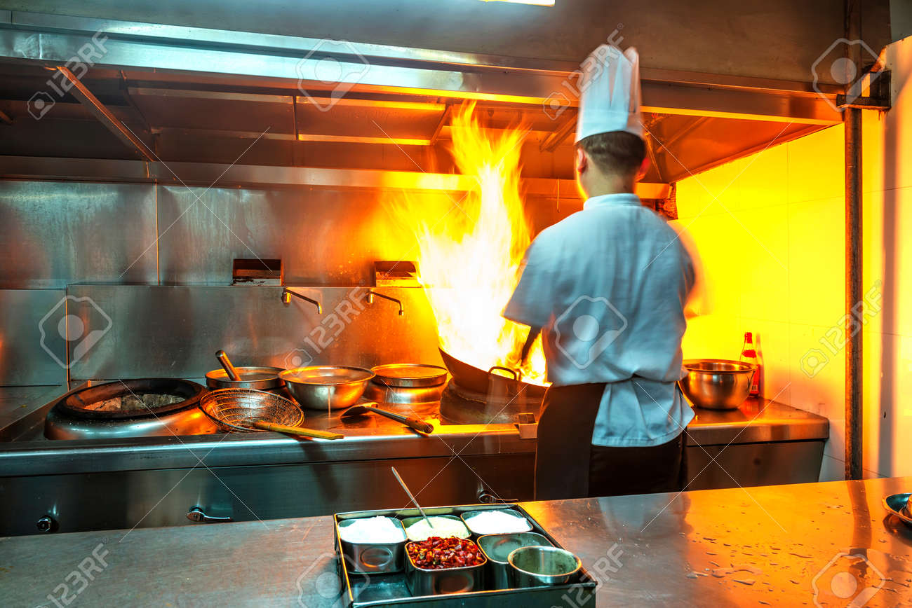 Chef in restaurant kitchen at stove with pan, doing flambe on food - 35899353