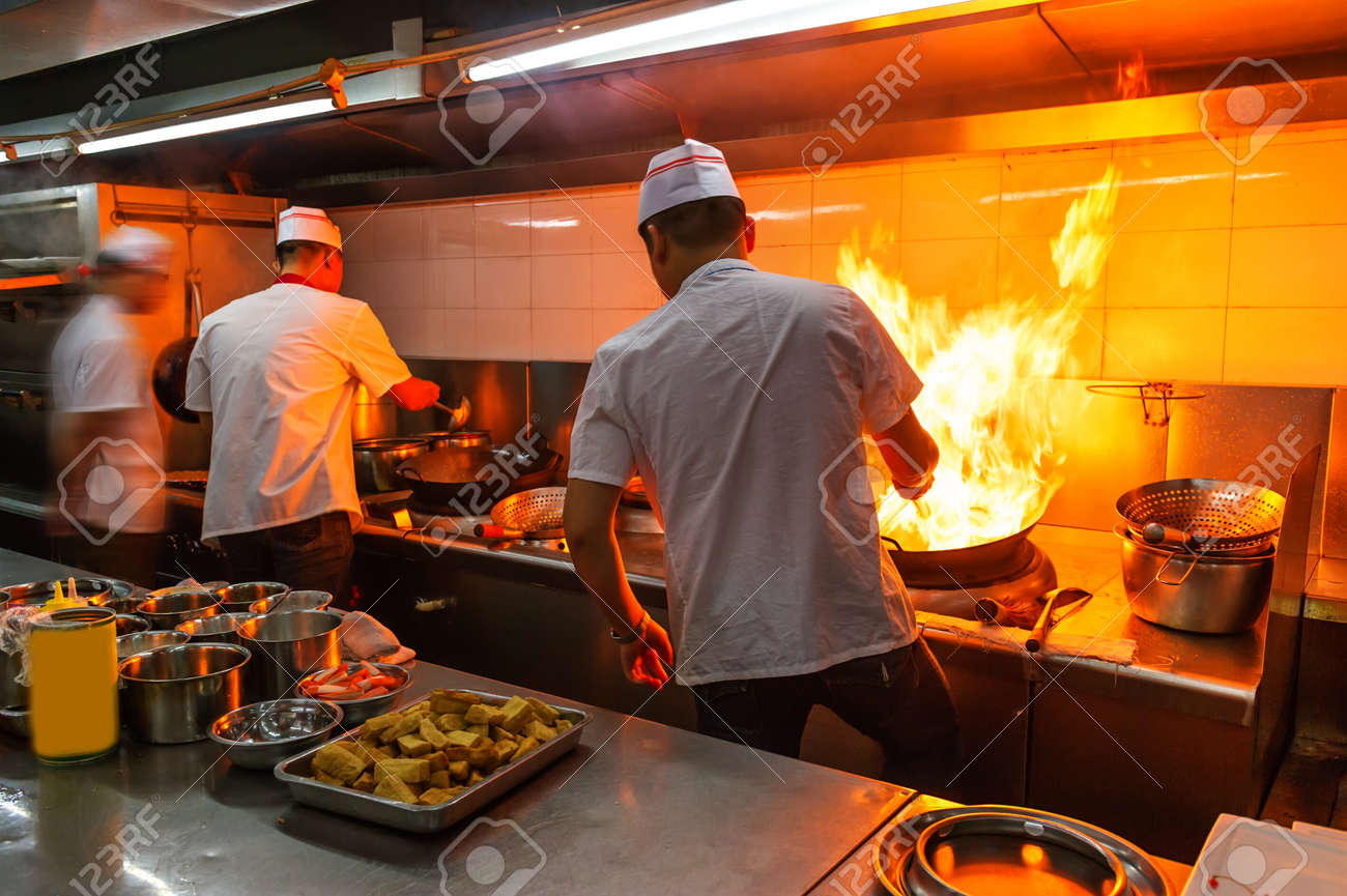 Crowded kitchen, a narrow aisle, working chef. - 49970610