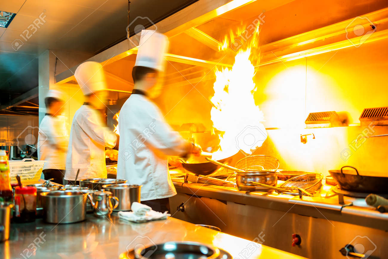 Restaurant Kitchen Chefs chef in restaurant kitchen at stove with pan, doing flambe on