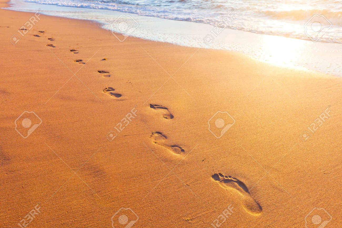 beach, wave and footsteps at sunset time - 18516188