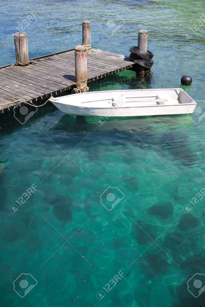 Stock Photo - view of small boat park at wood jetty with crystal clear asian  water