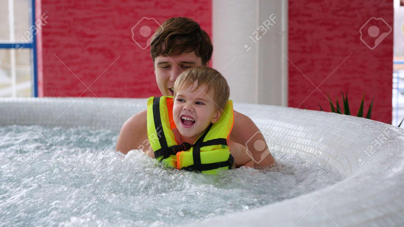 Un Jeune Pere Avec Un Enfant Nage Dans La Piscine Du Spa Detente