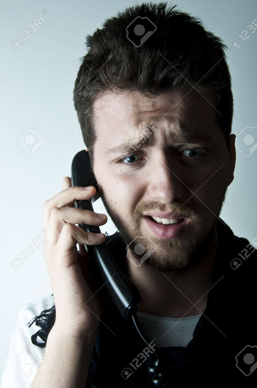Young man talking on a wired phone Stock Photo - 9069397