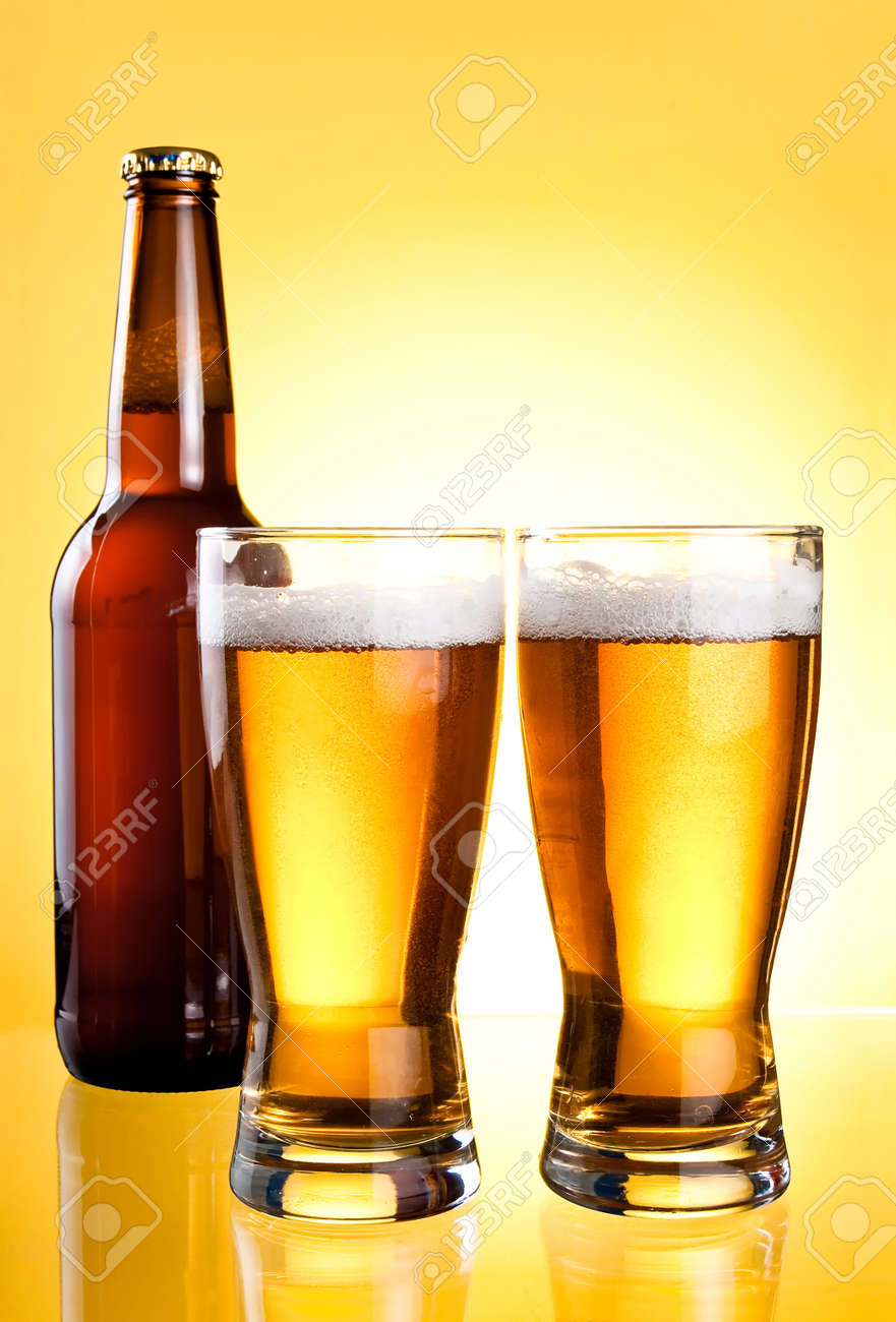 Two glasses and Bottle of fresh light beer on yellow background Stock Photo - 13871383
