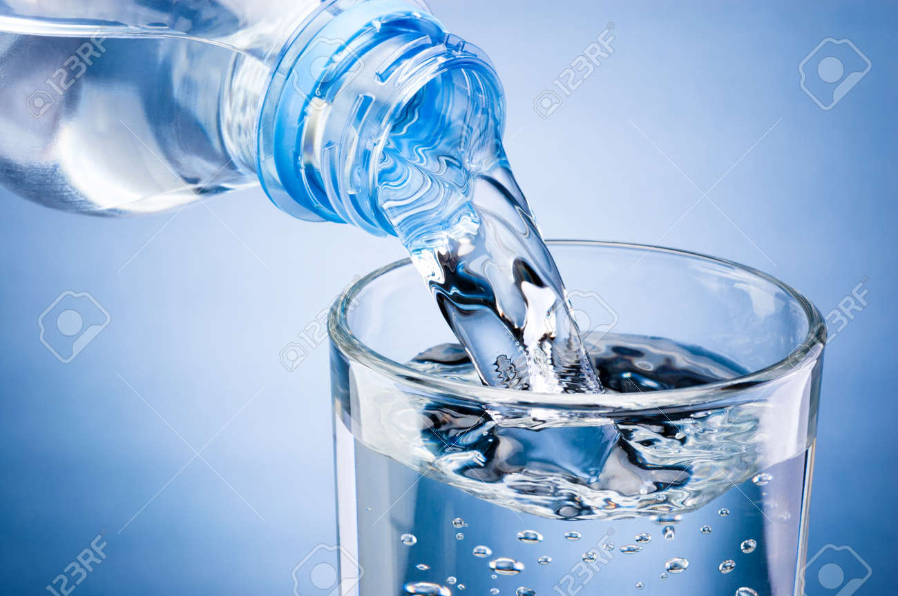 Pouring water from bottle into glass on blue background - 120729559