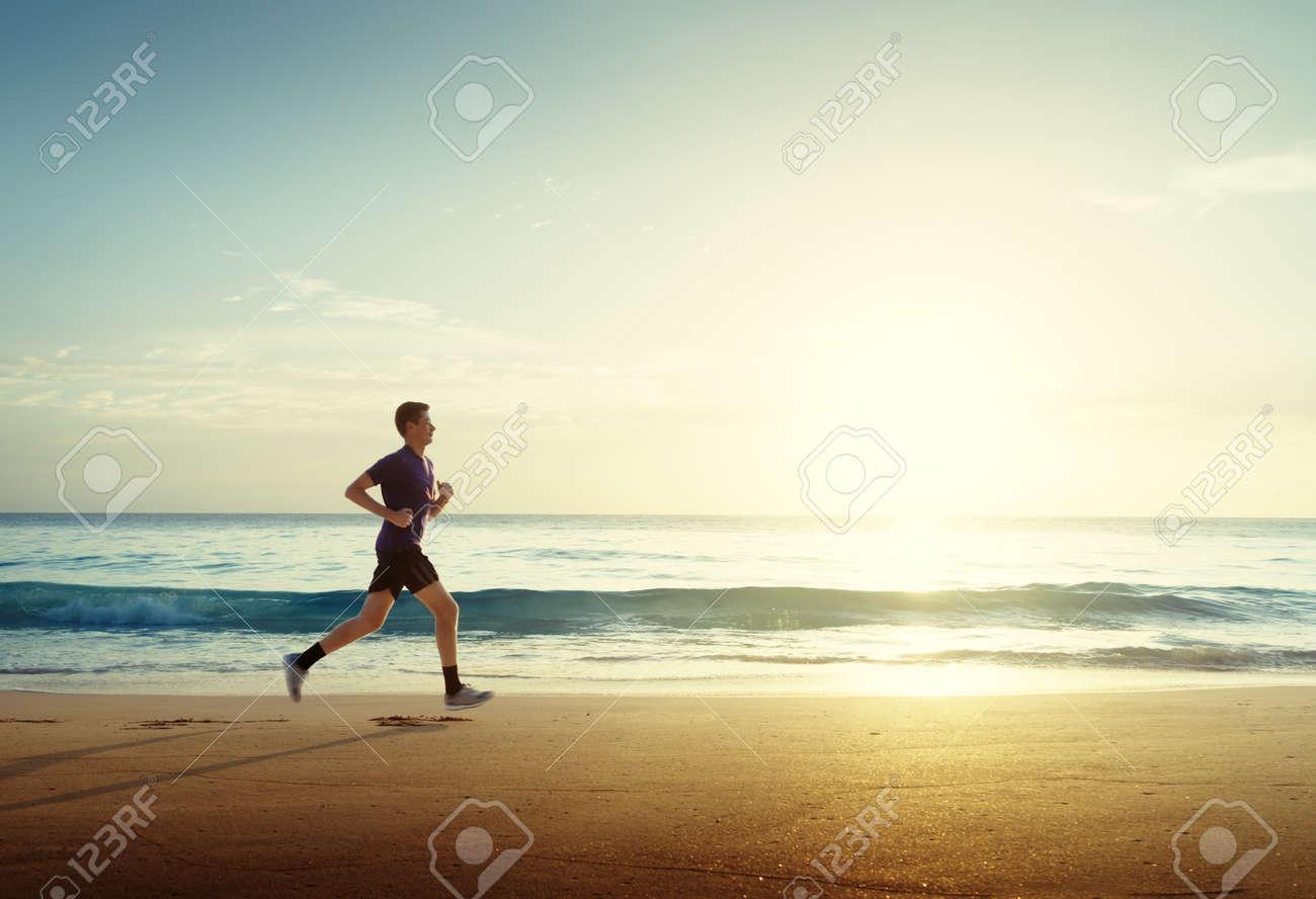 Man running on tropical beach at sunset - 56410885