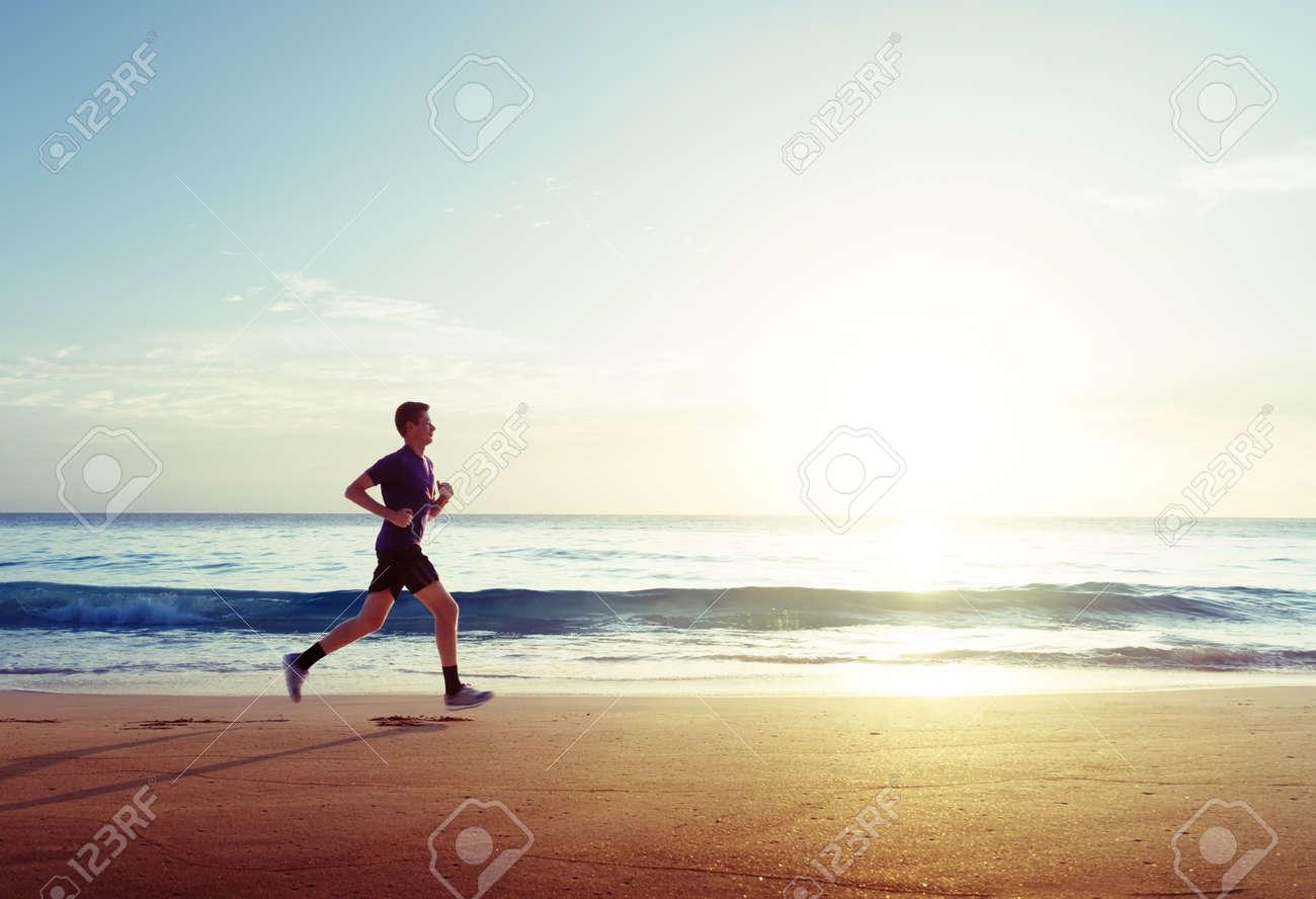 Man running on tropical beach at sunset - 56782695