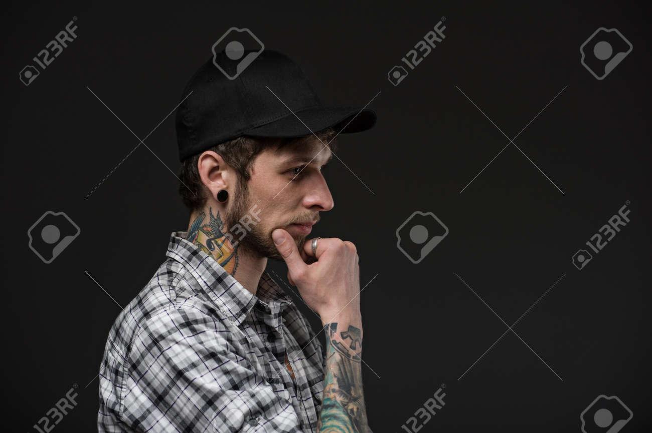 le profil d'un jeune homme avec le tatouage de cou. piercings dans