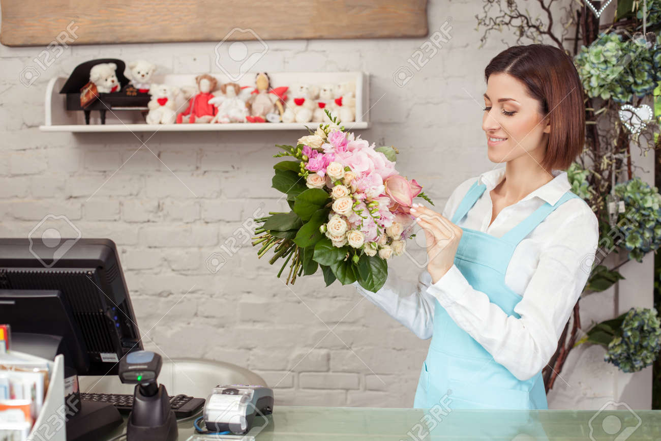 Beautiful florist is making a bouquet of roses she is looking beautiful florist is making a bouquet of roses she is looking at flowers with inspiration izmirmasajfo Gallery