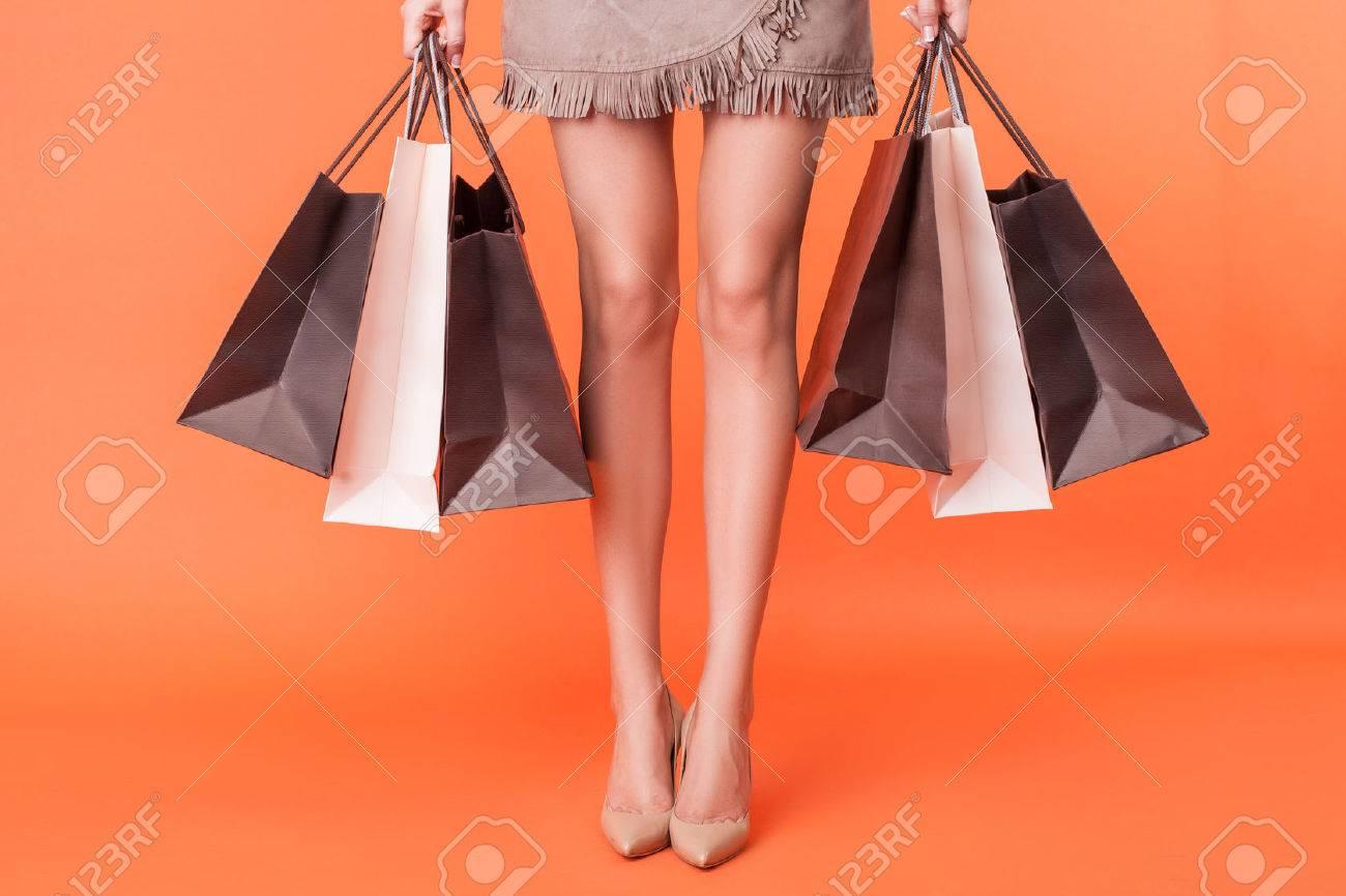 Primo piano di gambe femminili con scarpe su tacchi alti. La ragazza è in piedi e tenendo molti pacchetti di cose acquistate. Isolato su sfondo