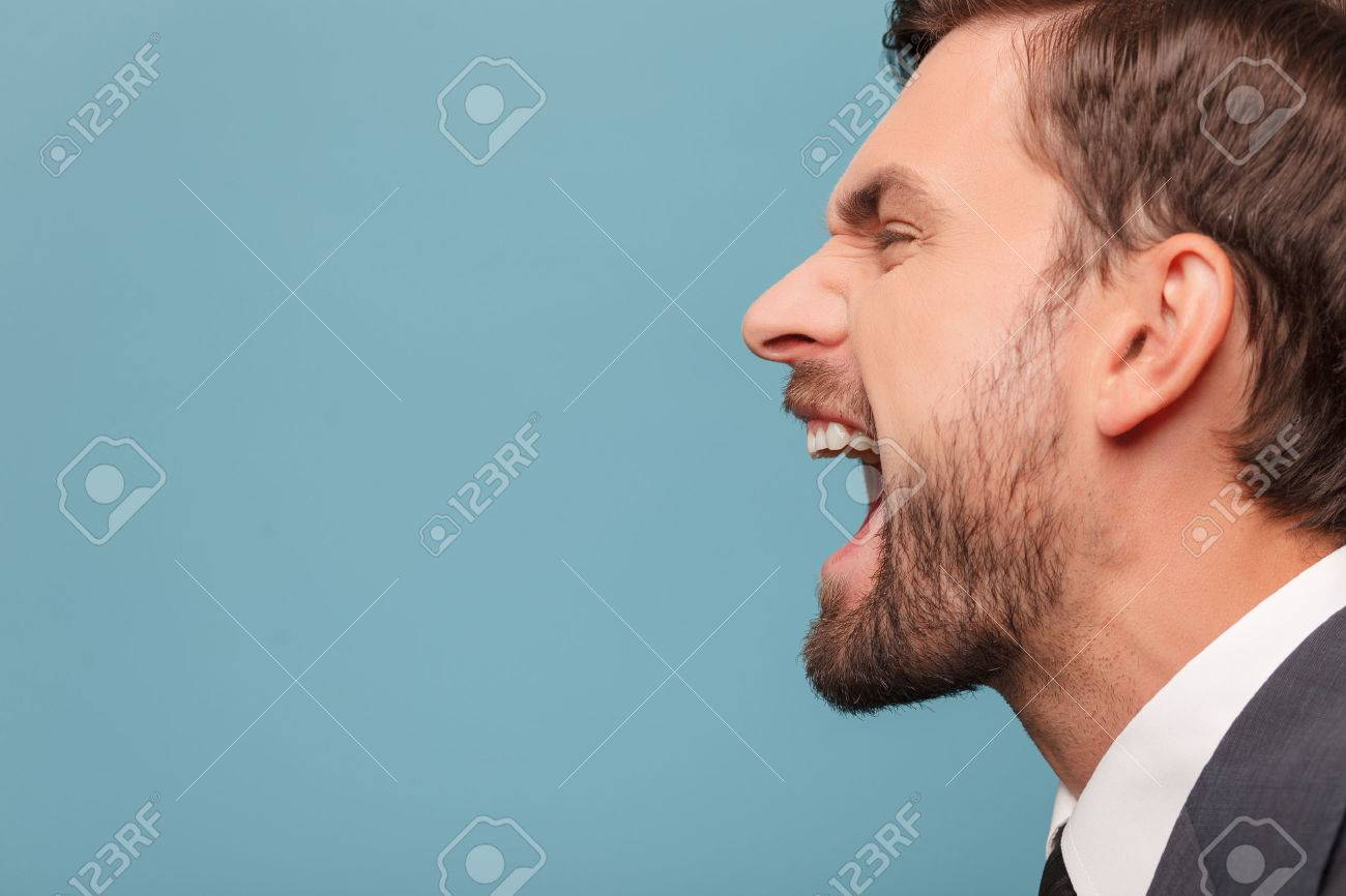 Close up of face of man shouting with anger. He is standing in profile. Isolated on blue background. Copy space in left side - 47925233