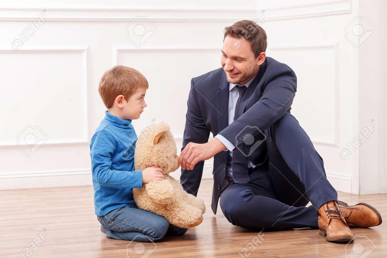 Fußboden Fröhlich ~ Fröhlich kleines kind ist auf dem fußboden in der nähe seines