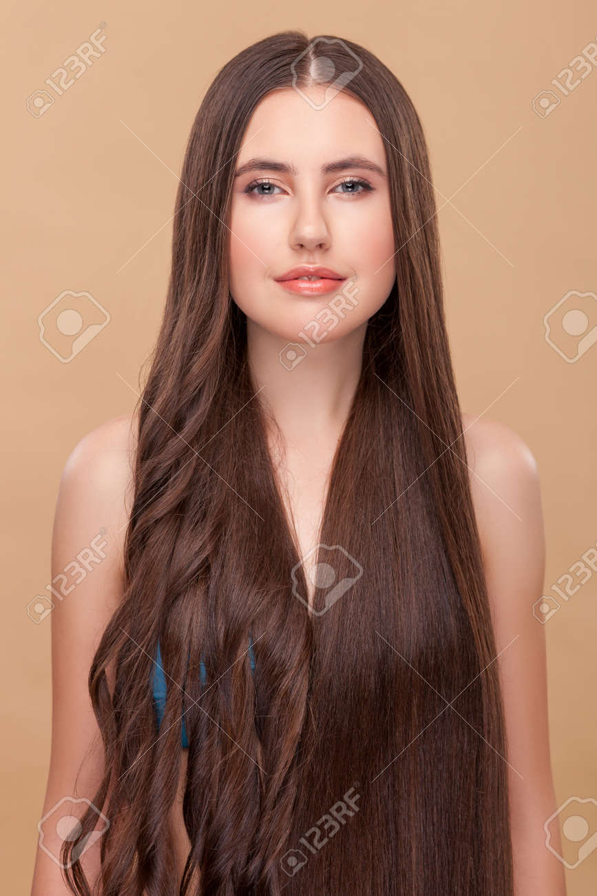 beautiful girl is experimenting with her long hair. she has curly..