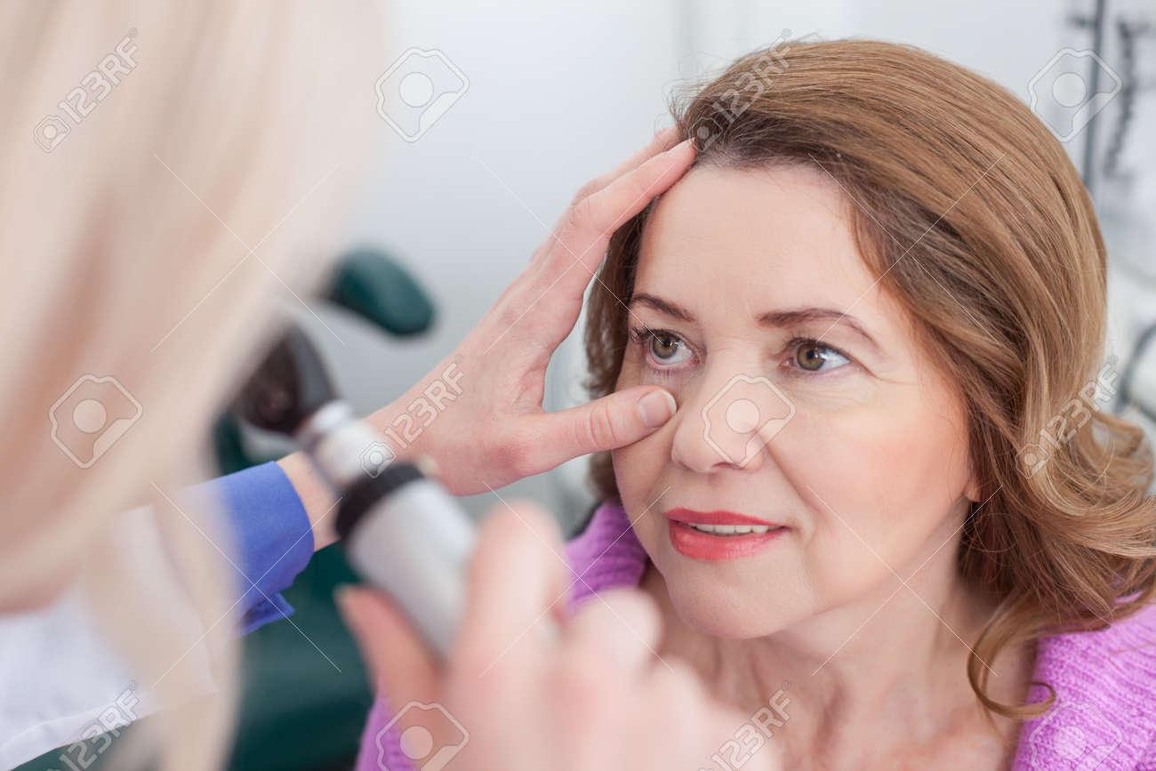 Banque d images - Oculiste Habile examine yeux des femmes dans la clinique.  Elle tient un outil spécial et diriger laser sur les yeux des femmes. 6071a92f9db8