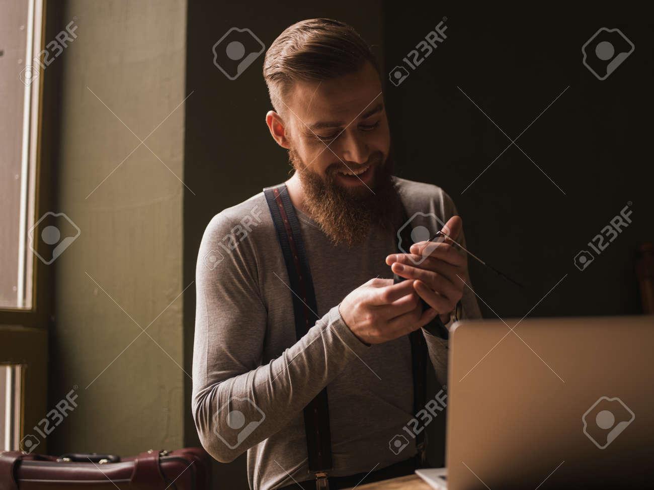 qualità le più votate più recenti shopping Waist fino Ritratto di uomo con la barba in stile retrò abbigliamento. Sta  pulendo gli occhiali e sorridente. L'uomo è seduto vicino al computer ...