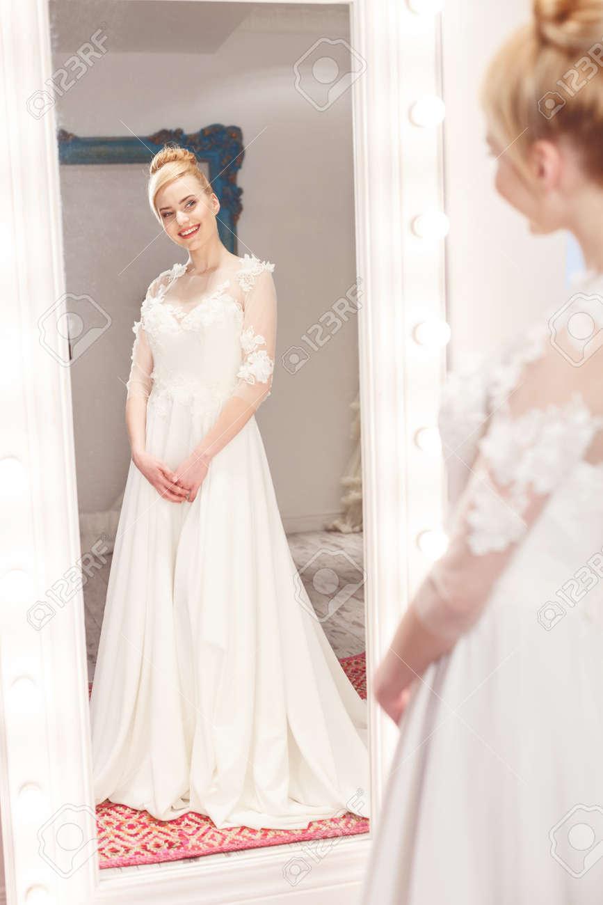 Atractiva Mujer Está De Pie En Un Vestido De Novia Blanco Ella Está Mirando El Espejo Y Sonriendo