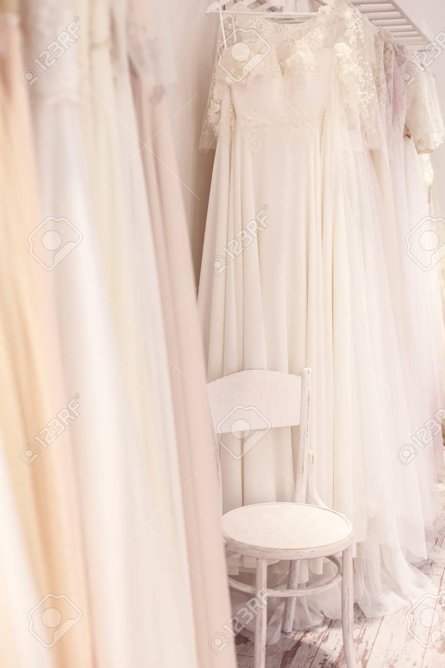 4a59b788bc71 Archivio Fotografico - Vasto assortimento di eleganti abiti da sposa appesi  a rack. C è una sedia tra di loro in boutique